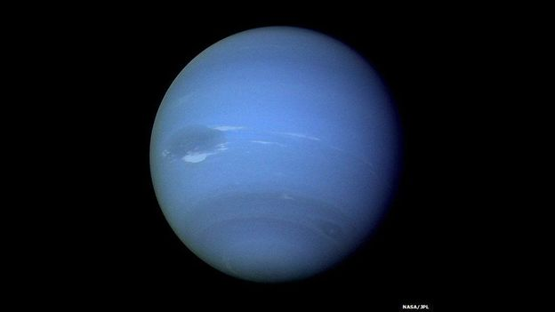 Neptuno, visto desde una de las cámaras del Voyager 2. La imagen fue tomada a una distancia de más de 7 millones de Km y muestra la Gran Mancha Oscura de Neptuno y el punto blanco que la acompaña.