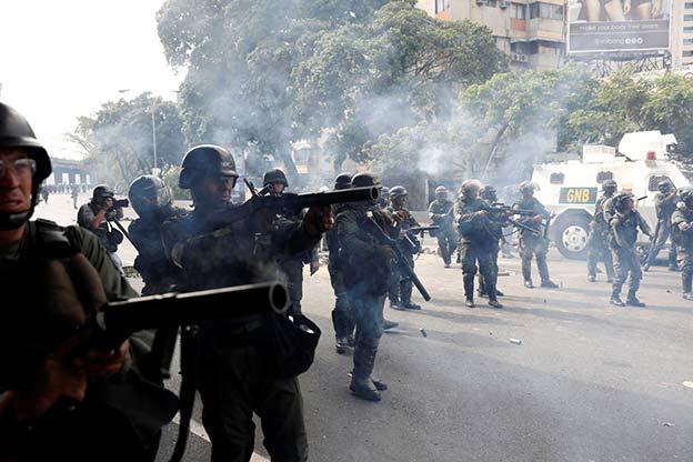 REUTERS/Carlos Garcia Rawlins Venezuelan national guard fire tear gas towards demonstrators during an opposition rally in Caracas, Venezuela