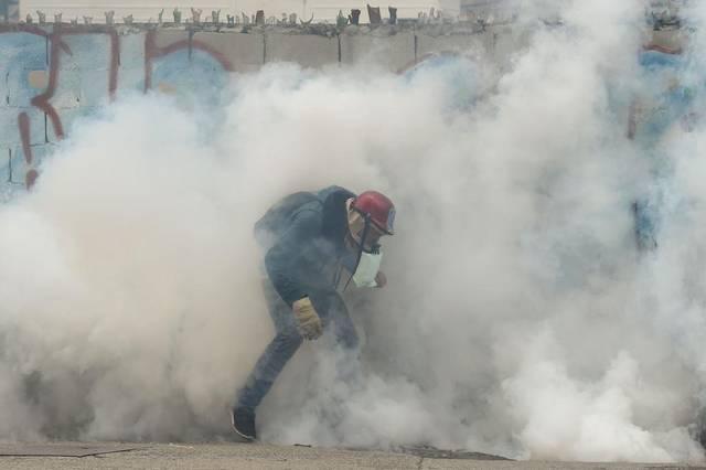 Gases lacrimógenos cubren a un manifestante opositor este jueves 20 de abril de 2017 en Caracas. Imagen: El Nuevo Herald
